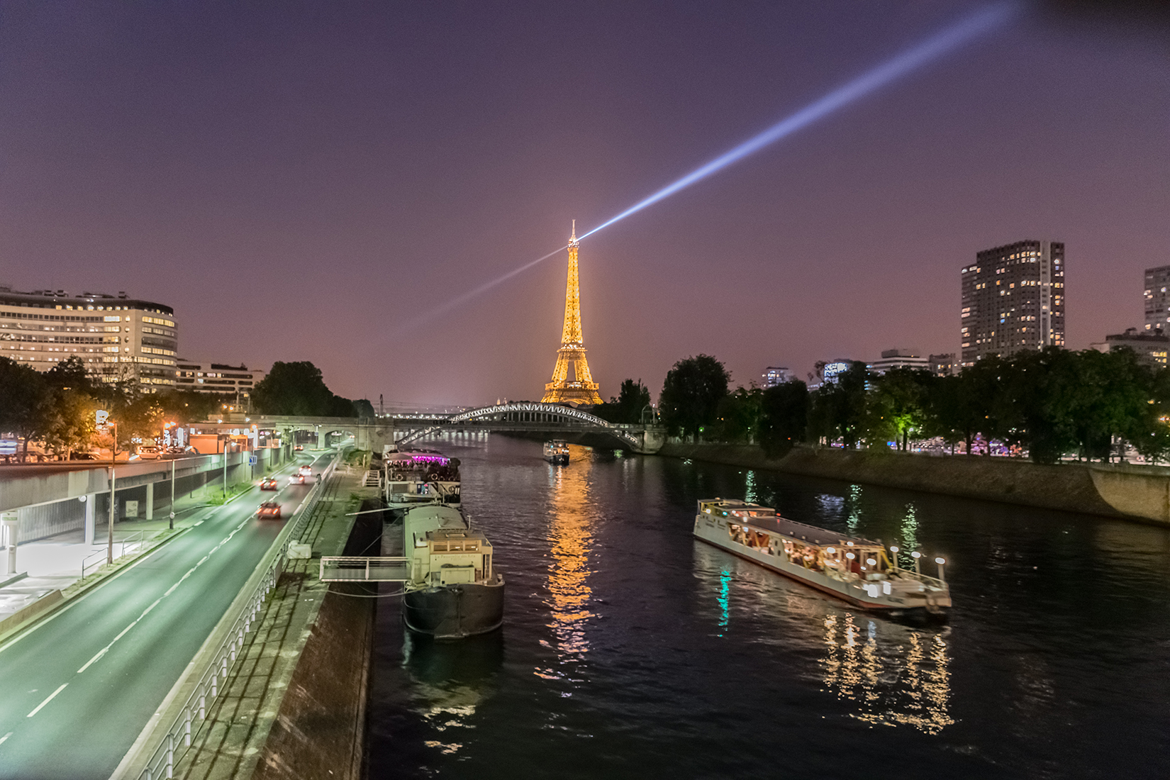 The Eiffel Tower illuminated at night. Here seen from the Pont du Garigliano bridge over the Seine in the west of the city