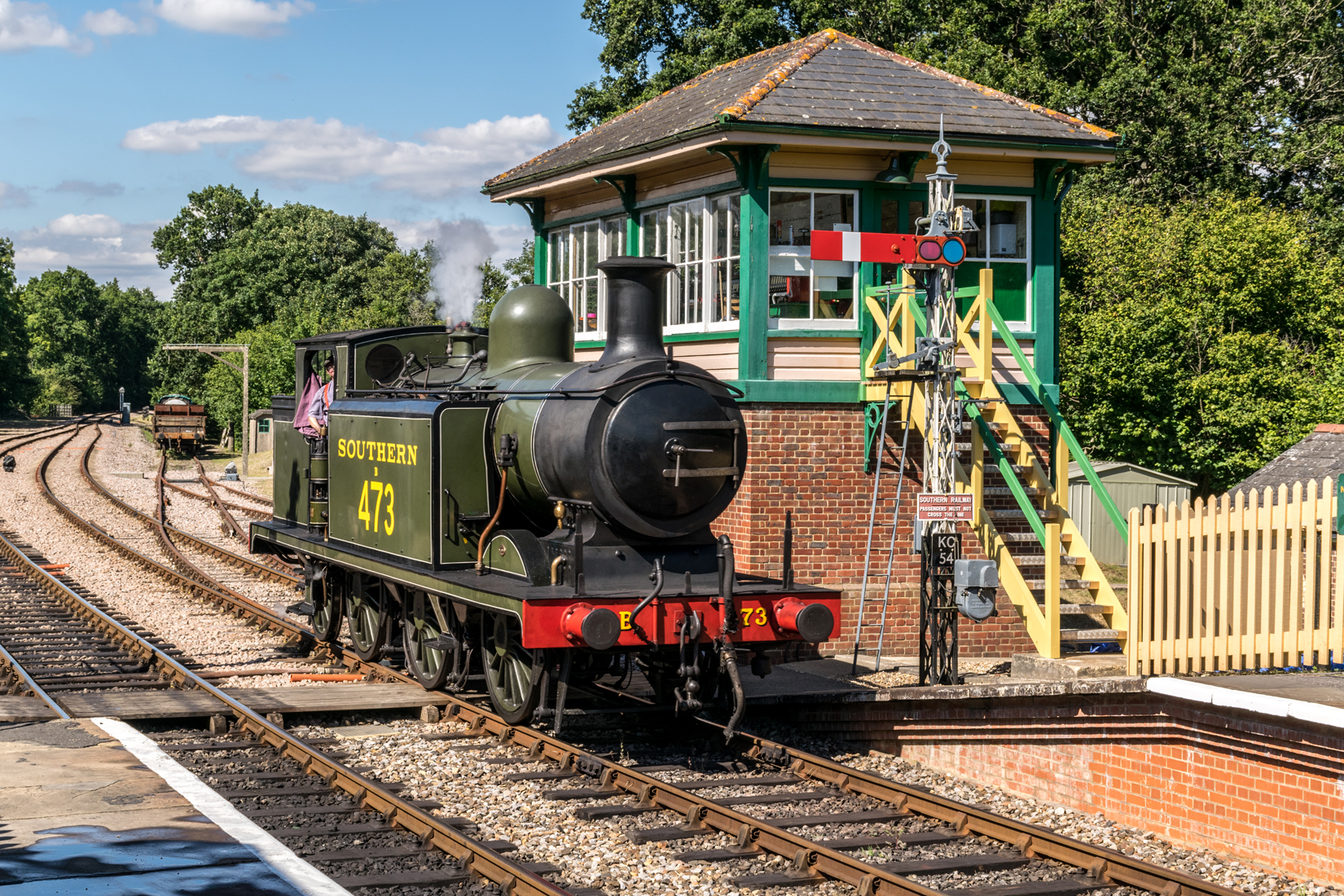 B473 pausing at Kingscote station signal box before completing its run around the goods wagons